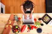 Woman using a Laptop while cooking — Stock Photo
