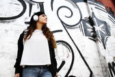 Girl listening to Music while leaning on a Wall — Stock Photo