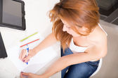 Roodharige meisje schrijven in keuken — Stockfoto
