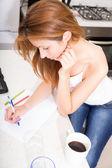 Redhead girl writing in kitchen — Zdjęcie stockowe