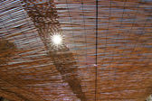 Sunshine shining through a thatched roof — Stock Photo