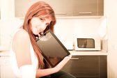 Young woman with a Tablet PC in the Kitchen — Stock Photo