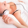 Blonde girl lying in bed listening to music — Stock Photo #48261047