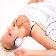 Blonde girl lying in bed listening to music — Stock Photo #48261089