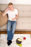 Young man with a Sandwich on the Sofa — Stock Photo