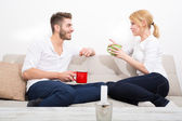 Young couple flirting on the Sofa  — Stock Photo