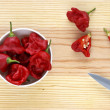 Hot chilli peppers in a bowl over a wooden table. — Stock Photo