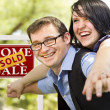 Happy Couple in Front of Sold Real Estate Sign - Stock Photo