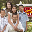 Stock Photo: Hispanic Family in Front of Sold Real Estate Sign