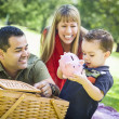 Stock Photo: Mixed Race Couple Give Their Son a Piggy Bank at the Park