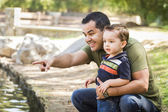 Hispanic Father Points with Mixed Race Son at the Park — Stok fotoğraf