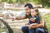 Spaanse vader punten met gemengd ras zoon in het park — Stockfoto