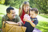 Mixed Race Couple Give Their Son a Piggy Bank at the Park — Stock Photo