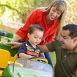 Young Mixed Race Boy Enjoys Toy Tractor with Parents — Stock Photo #13653256