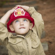 Adorable Child Boy with Fireman Hat Playing Outside - Stock Photo