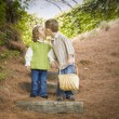 Two Children with Basket Kissing Outside on Steps - Stock Photo