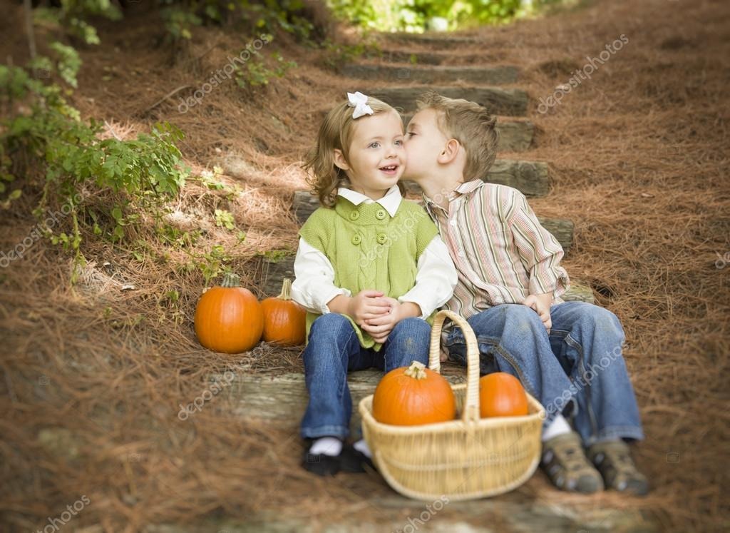 Adorable Brother and Sister Children Sitting on Wood Steps with Pumpkins Whispering Secrets or Kissing Cheek. — Stock Photo #13704202