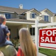 Family Looking at New Home with For Sale Real Estate Sign — Stock Photo #13840098
