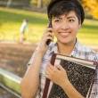 Mixed Race Female Student Holding Books and Talking on Phone — Stock Photo #14496753
