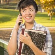 Mixed Race Female Student Holding Books and Talking on Phone — Stock Photo #14496767