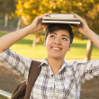 Royalty-Free Stock Photo: Mixed Race Female Student Holding Books on Her Head