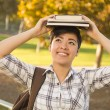 Mixed Race Female Student Holding Books on Her Head — Stock Photo
