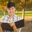 Mixed Race Young Female Holding Open Book and Pencil Outdoors - Foto Stock