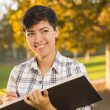 Royalty-Free Stock Photo: Mixed Race Young Female Holding Sketch Book and Pencil Outdoors