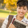 Portrait of a Pretty Mixed Race Female Student Holding Books - Stock Photo