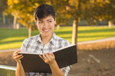 Mixed Race Young Female Holding Open Book and Pencil Outdoors — Stock Photo