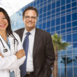 Hispanic Doctor or Nurse and Businessman in Front of Building — Стоковая фотография