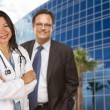 Hispanic Doctor or Nurse and Businessman in Front of Building — Stock Photo #15099467