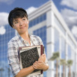 Mixed Race Female Student Holding Books in Front of Building - Stock Photo