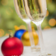 Christmas Ornaments and Champagne Glasses on Snow - Stock Photo