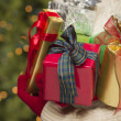 Woman Wearing Seasonal Red Mittens Holding Christmas Gifts - Stock Photo