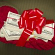 Woman Wearing Mittens Holding Stacks of Money with Red Ribbon — Stock fotografie