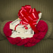 Woman Wearing Mittens Holding Stacks of Money with Red Ribbon — Stockfoto