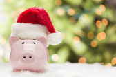 Pink Piggy Bank with Santa Hat on Snowflakes — Stock Photo