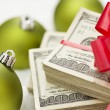 Stock Photo: Stack of Hundred Dollar Bills with Bow Near Christmas Ornaments