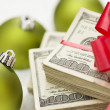 Stack of Hundred Dollar Bills with Bow Near Christmas Ornaments — Stock Photo #15960199