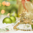 Stock Photo: Golden Christmas Reindeer Ornament Among Snow, Bulbs and Ribbon