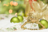 Golden Christmas Reindeer Ornament Among Snow, Bulbs and Ribbon — Stock Photo