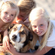 Stock Photo: Cute Sisters and Brother Playing with Dog