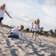 Adorable Brother and Sisters Having Fun at the Beach - Stock Photo