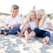 Adorable Sisters and Brother Having Fun at the Beach - Stock Photo