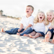 Cute Sibling Children Sitting at the Beach - Stock Photo