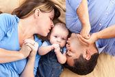 Smíšené rasy rodina s dítětem hrát na dece — Stock fotografie