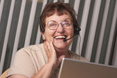 Smiling Senior Adult Woman with Telephone Headset and Monitor — Stock Photo