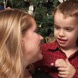 Adorable Son Talking to Mom in Front Of Christmas Tree — Stock Photo #16749187