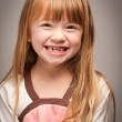 Fun Portrait of an Adorable Red Haired Girl on Grey — Stock Photo #16752253